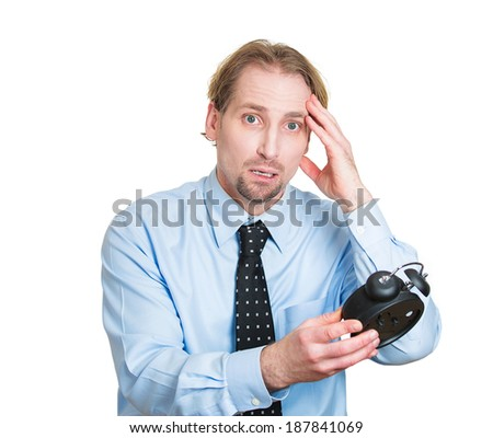 Closeup portrait young, stressed business man frustrated by lack of time to perform all duties for day, holding alarm clock, pressured by deadline, isolated white background. Busy corporate life style - stock photo