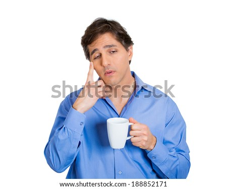 Closeup portrait young, tired, falling asleep business man holding cup coffee, struggling not to crash, stay awake, keep eyes opened, isolated white background. Human emotion, facial expressions