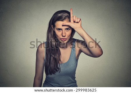 Closeup portrait young unhappy woman giving loser sign on forehead, looking at you, disgust on face isolated on gray wall background. Negative human emotion facial expression - stock photo