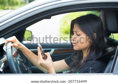 Closeup portrait, young woman driving in black car and checking her phone, annoyed by navigation gps system or bad text message or email, isolated outdoors background - stock photo