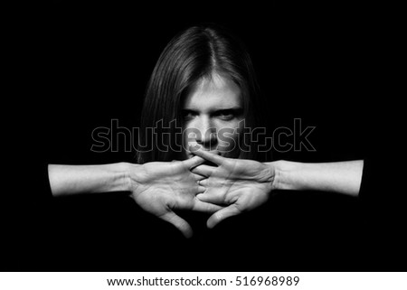 Closeup portrait young woman hiding mouth by hands, showing speak no evil concept, isolated on black background. Human emotion, expression, rights & communication. Copy-space. Monochrome studio shot