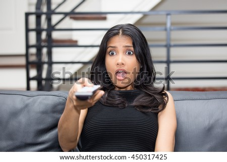 Closeup portrait, young woman in black shirt sitting on leather couch, watching TV, holding remote, surprised at what she sees,  isolated indoors flat background