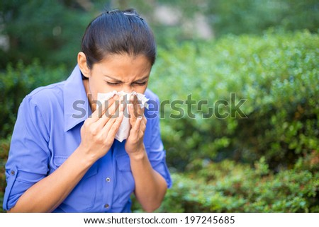 Closeup portrait, young woman in blue shirt with allergy or cold, blowing her nose with a tissue, looking miserable unwell very sick, isolated outside green trees background. Flu season, vaccination. - stock photo