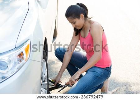 Closeup portrait, young woman in pink tanktop and blue jeans fixing flat tire with jack and tire iron, isolated green trees and road outside background. Roadside assistance concept - stock photo
