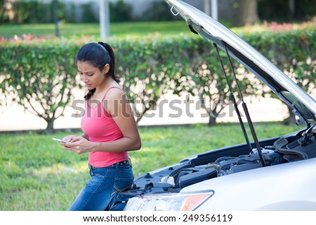 Closeup portrait, young woman in pink tanktop having trouble with her broken car, opening hood and texting for help on cell phone, isolated green trees and shrubs outside background - stock photo