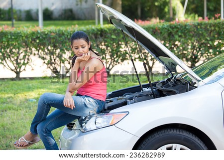 Closeup portrait, young woman in pink tanktop having trouble with her broken car, sitting on open hood engine worried, isolated green trees and shrubs outside background - stock photo
