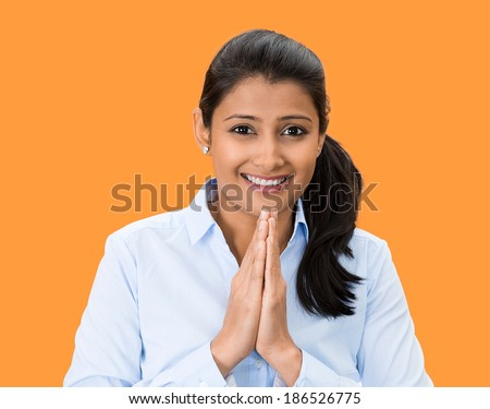 Closeup portrait, young woman praying looking at you, in gratitude, thankfulness and hope, isolated orange background. Positive human emotions, facial expression feelings, reaction - stock photo