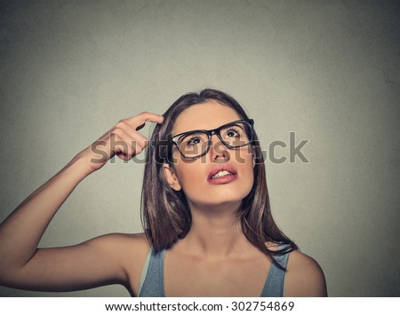 Closeup portrait young woman scratching head, thinking daydreaming deeply about something looking up isolated on gray wall background. Human facial expressions, emotions, feelings, signs, symbols - stock photo