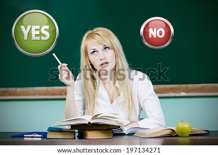 Closeup portrait young woman student sitting at desk in classroom, deciding thinking with yes, no choice, looking up isolated chalkboard background. Human facial expressions, life perception reaction  - stock photo