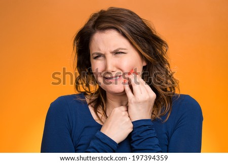 Closeup portrait young woman with sensitive tooth ache, crown problem crying from pain, touching outside mouth with hand isolated orange background. Negative emotion, facial expression feeling, health - stock photo