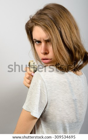 Closeup portraityoung woman holding dollar banknotes tightly isolated grey wall background. Negative human emotion facial expression feeling - stock photo