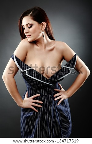 Closeup pose of big breasted sexy woman on gray background, hand in waist - stock photo
