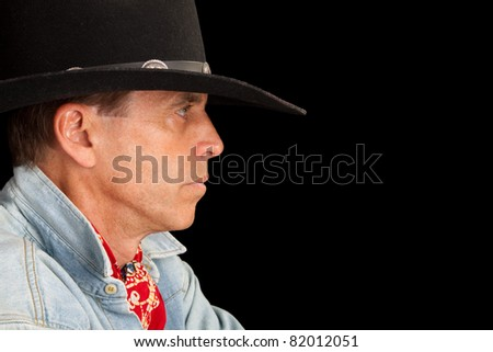 Closeup profile of a handsome man in a cowboy outfit.