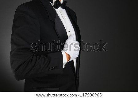 Closeup profile of a man wearing a tuxedo and white gloves holding his lapel. Horizontal format on a light to dark gray background. Man is unrecognizable. - stock photo