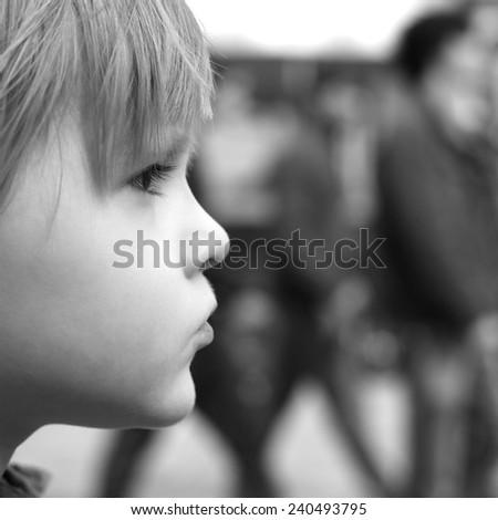 Closeup profile of a thoughtful child, monochrome  - stock photo