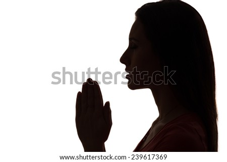 closeup profile of a woman praying in silhouette isolated - stock photo