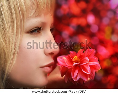 Closeup profile of beautiful blond woman with flower on red background - stock photo