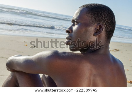 Closeup profile of shirtless lean African American man with intense expression sitting and thinking on sandy beach - stock photo