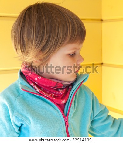 Closeup profile portrait of cute Caucasian blond girl over yellow wooden wall - stock photo