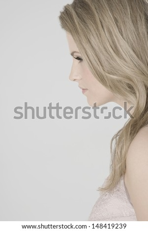 Closeup profile shot of a sexy young woman against gray background - stock photo