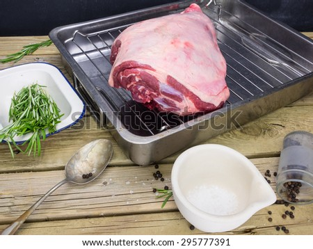 closeup raw leg of lamb joint on roasting tin with ingredients for roast lamb: salt pepper and fresh rosemary - stock photo