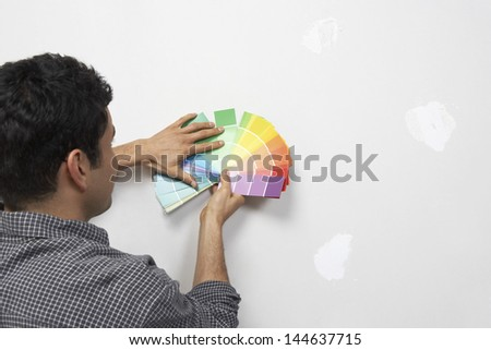 Closeup rear view of a man holding paint color samples against wall