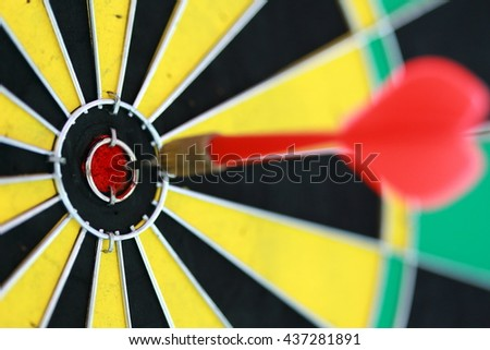 closeup red dart arrow hitting in target bullseye of a dartboard, business solutions, and success concept - stock photo