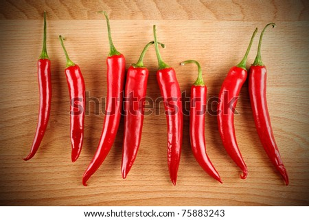 closeup red hot peppers on wood board - stock photo