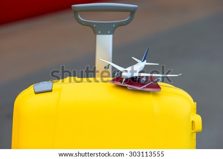 Closeup red passports and airplane small model on yellow luggage at train station - stock photo