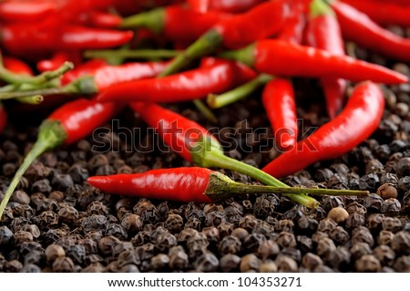 closeup red peppers on black peppercorns - stock photo
