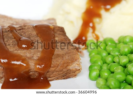 Closeup roast beef with gravy and vegetables - stock photo