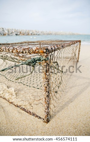 closeup rusty crab pot on the sandy beach at sunny day. focus in the middle - stock photo