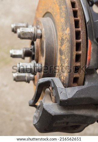 Closeup rusty disc brake with bolts and nuts fixing in garage