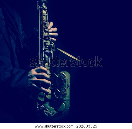 Closeup saxophone in player action on a dark background, dark blue tone - stock photo