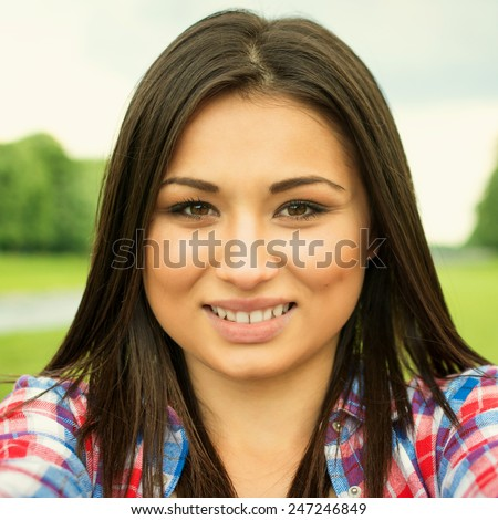 Closeup seflie of cute teenage mixed race teenage girl outdoors in summer. No filter, retouched, square format. - stock photo