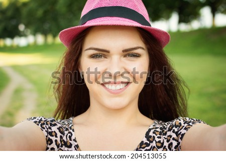 Closeup selfie shot of cute young woman with pink hat and animal print shirt. Beautiful teenage Caucasian girl posing for a self portrait outdoors in park on sunny summer day. - stock photo