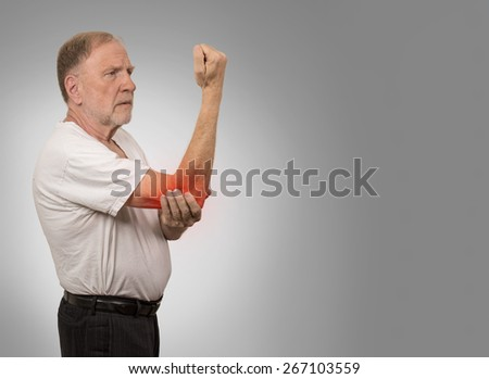 Closeup senior man with elbow inflammation colored in red suffering from pain and rheumatism isolated on gray wall background with copy space  - stock photo