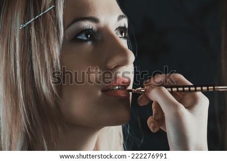 Closeup shoot of beautiful young caucasian model getting fashion make-up - stock photo