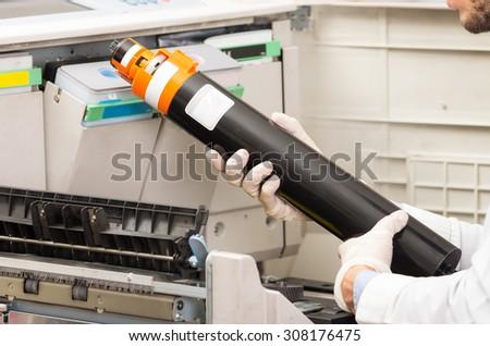 closeup shot hans changing toner cartridge in digital photocopier machine - stock photo