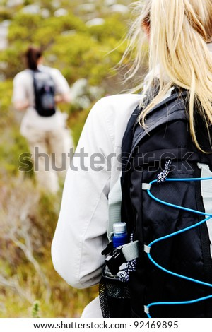 closeup shot of a backpack on a woman's back hiking outdoors - stock photo