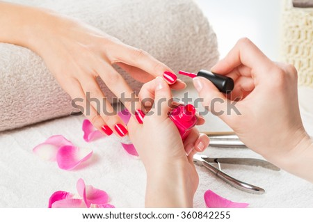 Closeup shot of a beautician applying nail polish to female nail in a nail salon. Close up of a woman hand with pink nailpolish after the manicure. 