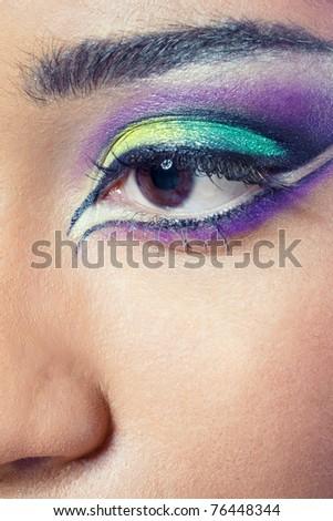 Closeup shot of a beautiful young woman's eye with colorful makeup - stock photo