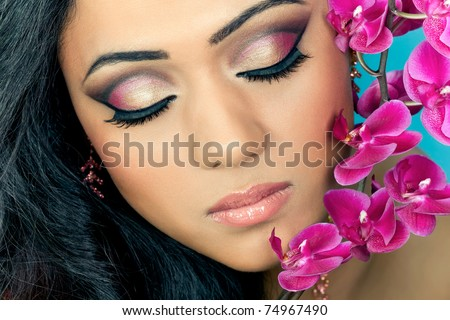 Closeup shot of a beautiful young woman's face with purple orchid flowers - stock photo