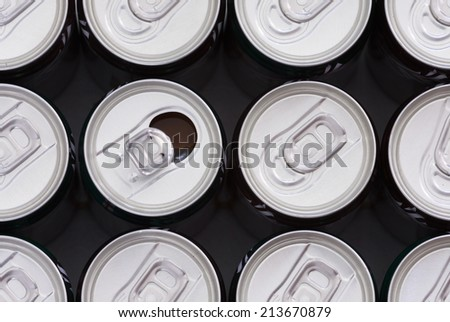 closeup shot of a bunch of soft drink cans with opened one