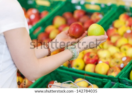 Closeup shot of a female customer comparing different apples at the food counter. - stock photo