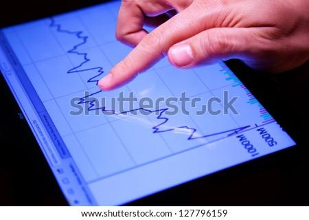 Closeup shot of a Hand Touching a Stock Exchange Chart - stock photo