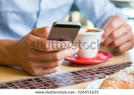 Closeup shot of a man texting on mobile phone. Guy is holding a modern smartphone and writing a phone message at breakfast table. Man's hand holding the smartphone while drinking a cup coffee.  - stock photo