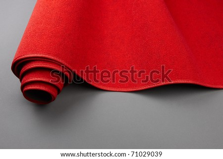 Closeup shot of a red carpet being rolled up, includes space for copy - stock photo