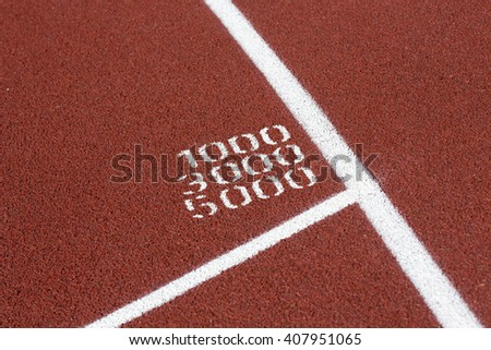 Closeup shot of a running track showing the race lengths. The track is recently renewed. The lengths are 1000, 3000 and 5000 meters. - stock photo