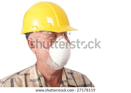Closeup shot of a senior construction worker in a hardhat and face mask - stock photo